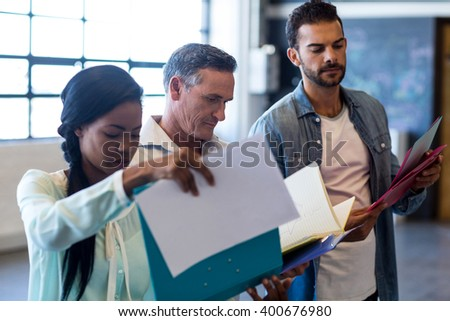Colleagues looking at file in the office - stock photo