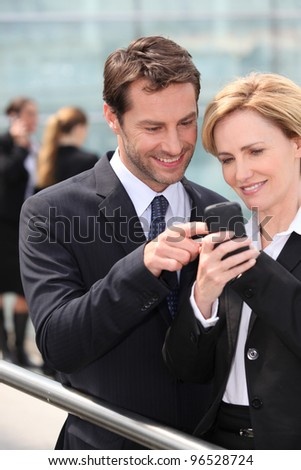 Colleagues looking at phone - stock photo