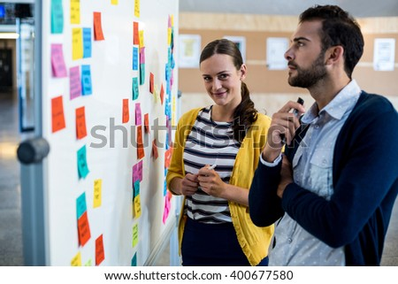 Colleagues looking at sticky notes on white board in the office - stock photo