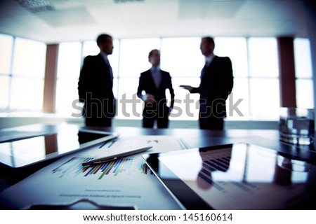 Colleagues meeting to discuss their future financial plans, only silhouettes being viewed - stock photo