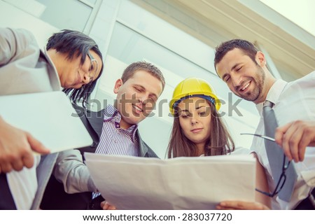 Colleagues reading construction documents in front of building - stock photo