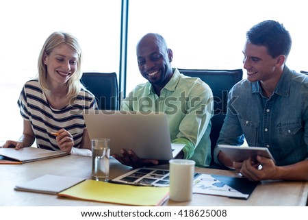 Colleagues sitting at their desk in the office - stock photo