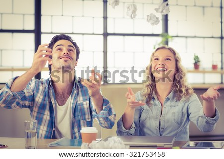 Colleagues smiling and looking up while relaxing at office - stock photo