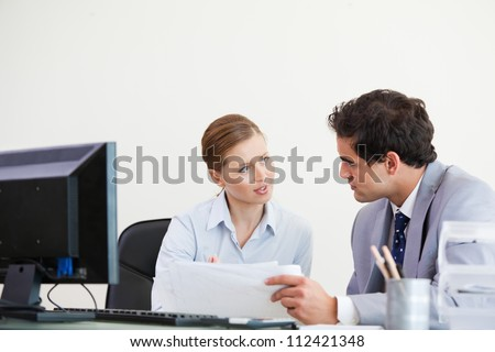 Colleagues talking while holding a sheet against grey background - stock photo