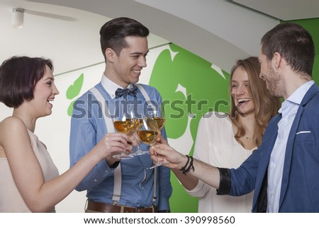 Colleagues toasting with rose wine celebrating their anniversary in a gourmet restaurant - stock photo