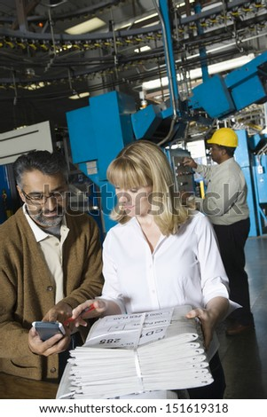 Colleagues using calculator and checking newspaper with worker in background at factory - stock photo