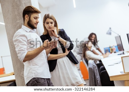 Colleagues using phone in an office and talking