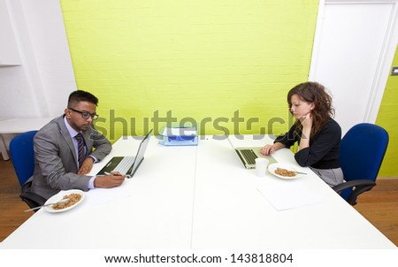 Colleagues working at their desks - stock photo