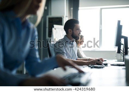 Colleagues working on computers in an office. - stock photo