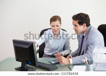 Colleagues working together on a computer against grey background - stock photo