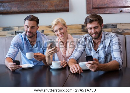 Colleagues working with smartphones at the cafe - stock photo