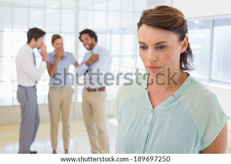 Colleauges gossiping with sad young businesswoman in foreground at a bright office - stock photo