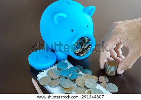 Collect money from saving in Piggy Bank, Hand holding money from Piggy Bank