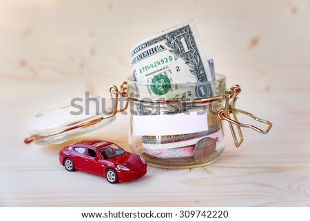 Collecting money for new car. Glass tin as moneybox with cash savings (banknotes and coins) and toy car on  wooden background. White empty space for your text. - stock photo