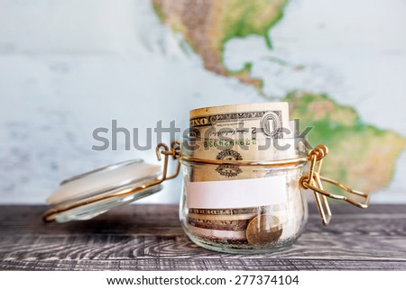 Collecting money for travel. Glass tin as moneybox with cash savings (banknotes and coins) on wooden table and map as background. White empty paper for text. - stock photo