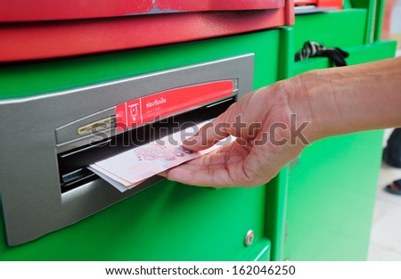 collecting Thai Baht 100 notes at ATM machine - stock photo