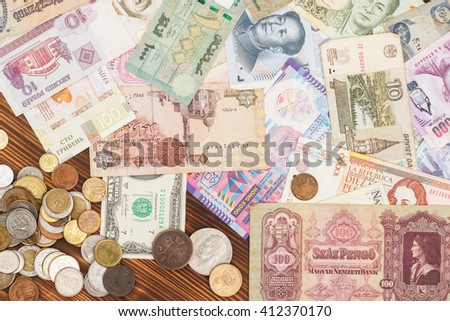 Collection from different money bills and coins on the wooden background