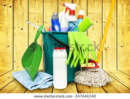 Collection from tools for cleaning in a bucket on wooden background - stock photo