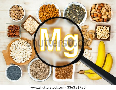 Collection natural products containing magnesium - pumpkin seeds, poppy seed, cashew nuts, beans, raw cocoa beans, almonds, sunflower seeds, oatmeal. buckwheat, peanuts, hazelnuts, pistachios, banana - stock photo