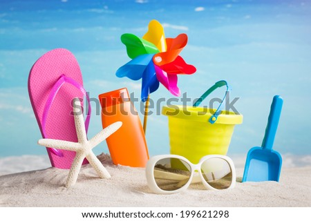 Collection of beach items - flip-flops, starfish, sunglasses, lotion, child's bucket, spade and other toys  - stock photo