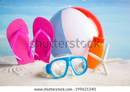 Collection of beach items -  flip-flops, sunglasses, lotion and beach ball  - stock photo