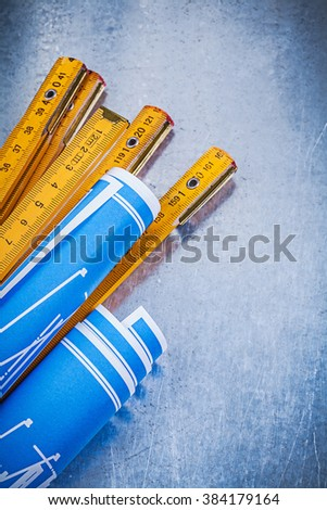 Collection of blue rolled blueprints wooden meter on metallic background.