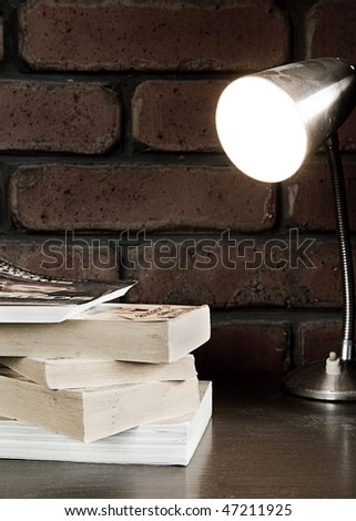Collection of books sitting on a table under a lamp - stock photo