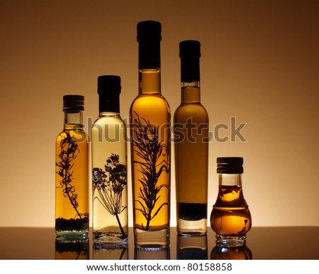 Collection of bottles of olive oil illuminated from behind and underneath the bottles. The bottles has olive oil with pepper, rosemary and other seasonings. - stock photo