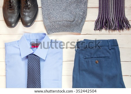 collection of business modern men's clothing: black shoes, blue shirt, tie, blue pants, pullover, scarf for business travel on a white wooden background.  Top view. Business concept. - stock photo