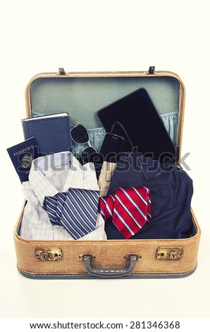collection of business travel items in a suitcase with a vintage filter  - stock photo