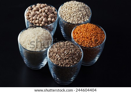 Collection of cereals and legumes in transparent cup on a black background - stock photo