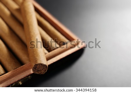 Collection of cigars in humidor on black table, closeup - stock photo