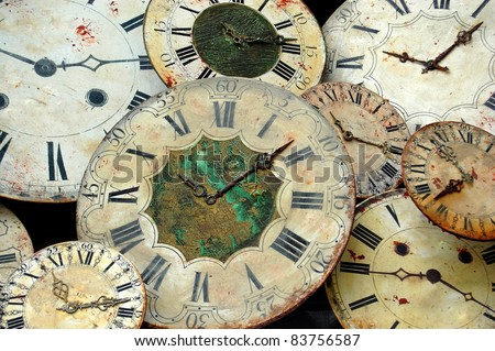 Collection of Clock Faces A collection of old clock faces piled up with roman numerals on their face. - stock photo