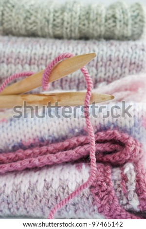 Collection of colorful knitted jumpers and vests stack in a pile.  Shallow depth of field. Focus on tips of wooden knitting needles.