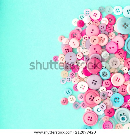 Collection of Colourful Sewing Buttons on Retro Turquiose Background with Copy Space - stock photo