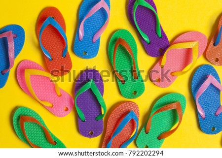 collection of colourful summer flip flop sandals on a bright yellow background