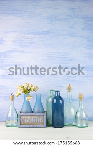 Collection of decorative bottles on blue wooden background. - stock photo