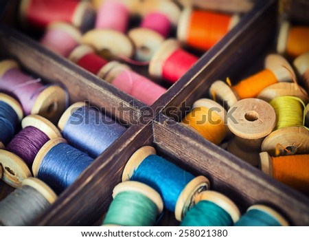 Collection of different color pools threads arranged in a grunge wooden box - stock photo