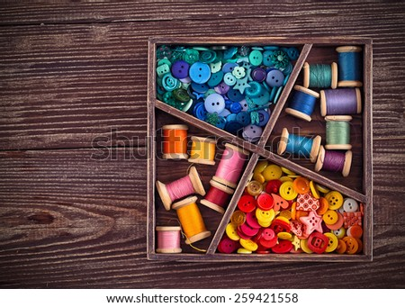 Collection of different color thread  arranged in a grunge wooden box - stock photo
