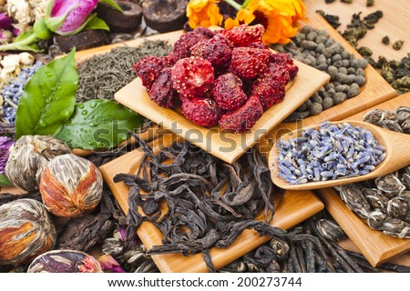 Collection of different dry types tea (green,black, herbal) in wooden spoon on kitchen table background, close up - stock photo