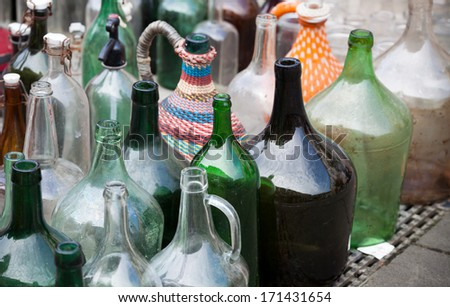 Collection of empty alcohol bottles in several colors on market - stock photo