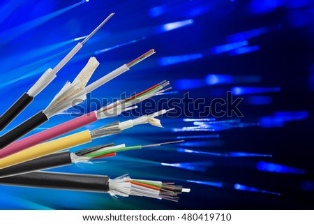 Collection of fiber optical cables on blurry technology background. Loose tubes with optical fibres and central strenght member, waterblocking glass yarn and ripcord, multimode or single mode