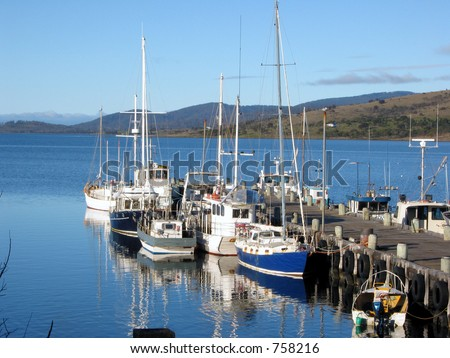 collection of fishing boats tied up at a jetty in Tasmania. Great weather! - stock photo