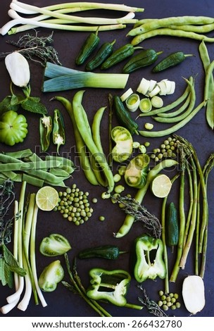 Collection of fresh green vegetables on blue metal table, asparagus, leek, string beans, french beans, fresh peas, lettuce, tomatoes, peppers, onions, radicchio. Organic and healthy vegetables. - stock photo