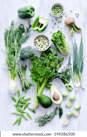 Collection of fresh green vegetables on white rustic background, broccoli, lettuce, celery, beans, capsicum, peppers, peas, brussels sprouts, kiwi, avocado, - stock photo