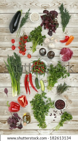 Collection of fresh green vegetables on white wood background, eggplant, parsley, white beans, tomatoes, parsley, beets, peppers, garlic, onions, cucumbers, red beans, thyme, salt, cabbage - stock photo