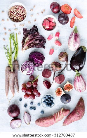Collection of fresh purple toned vegetables and fruits on white rustic background, eggplant, beetroot, carrot, fig, plum, aubergine, cabbage, grapes, radishes, loose leaf lettuce