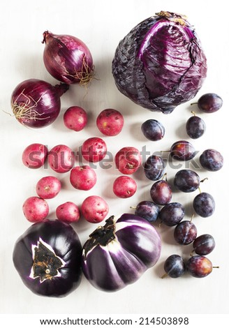Collection of fresh purple toned vegetables on white wooden background