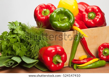 Collection of fresh raw vegetables in a wooden box; sweet and chili pepper, parsley, dill and leek  - fresh ingredients for cooking