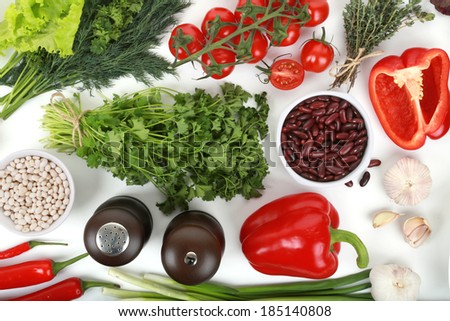 Collection of fresh vegetables on white background, parsley, white beans, tomatoes, parsley, peppers, garlic, onions, red beans, thyme, salt - stock photo